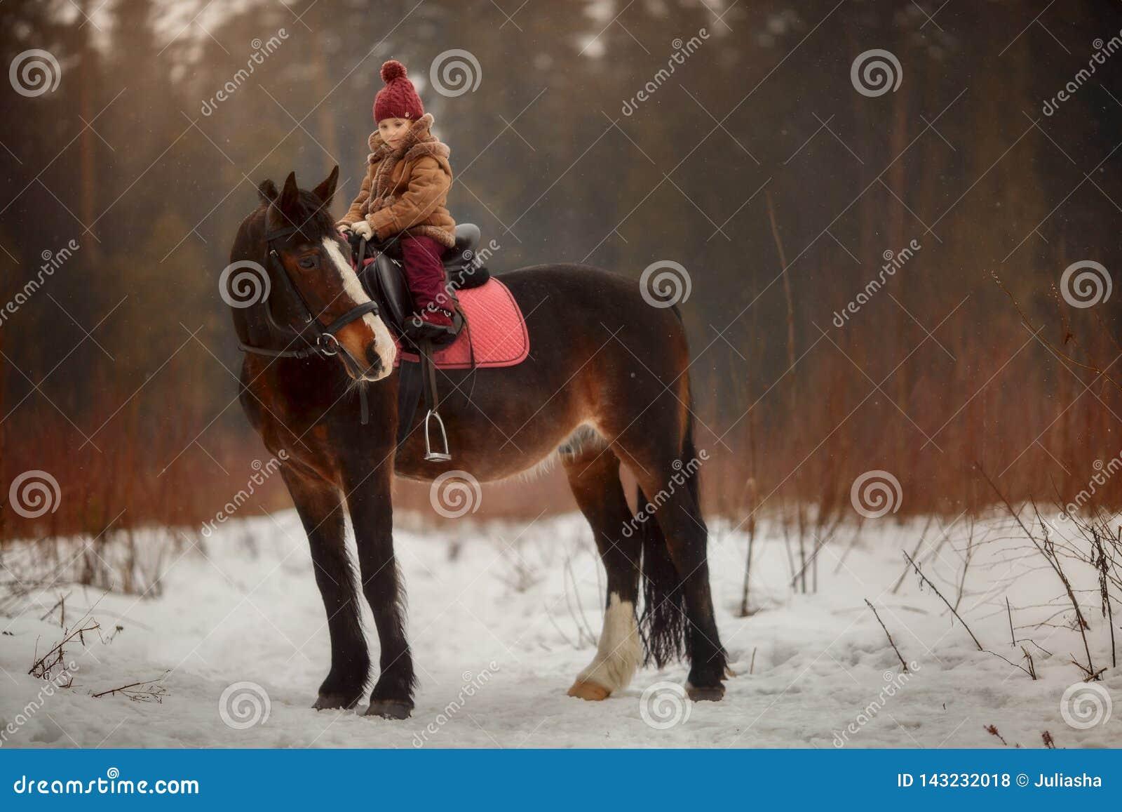 Liten flicka med den utomhus- ståenden för häst på vårdagen