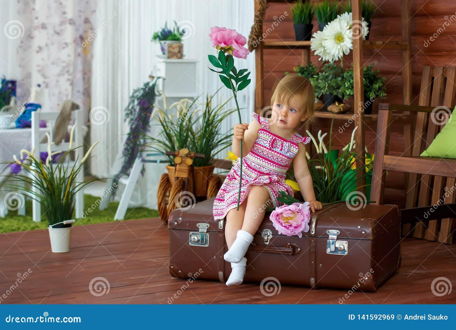 Liten flicka med en blomma på en resväska