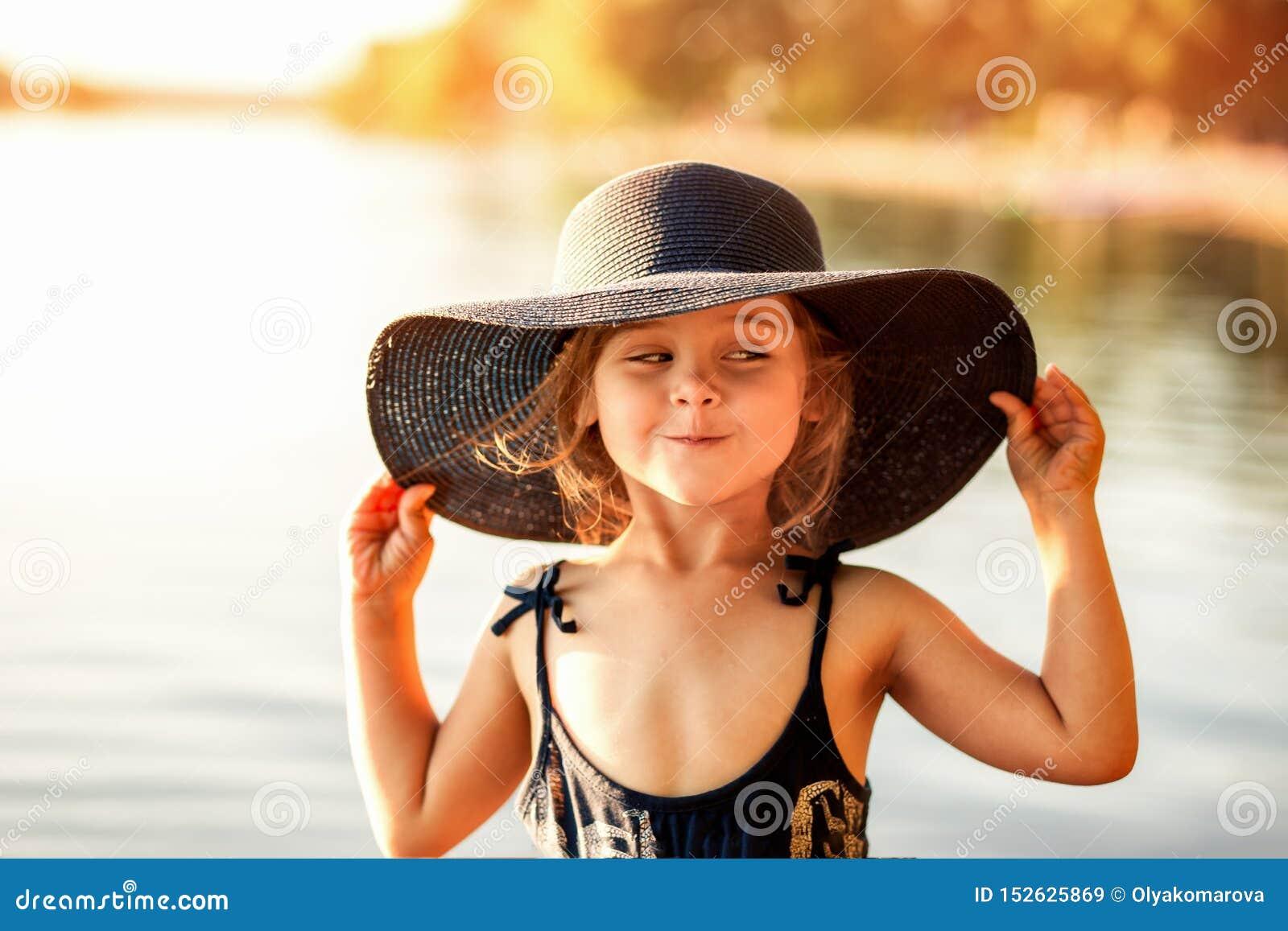 Liten flicka med en hatt vid floden i sommar