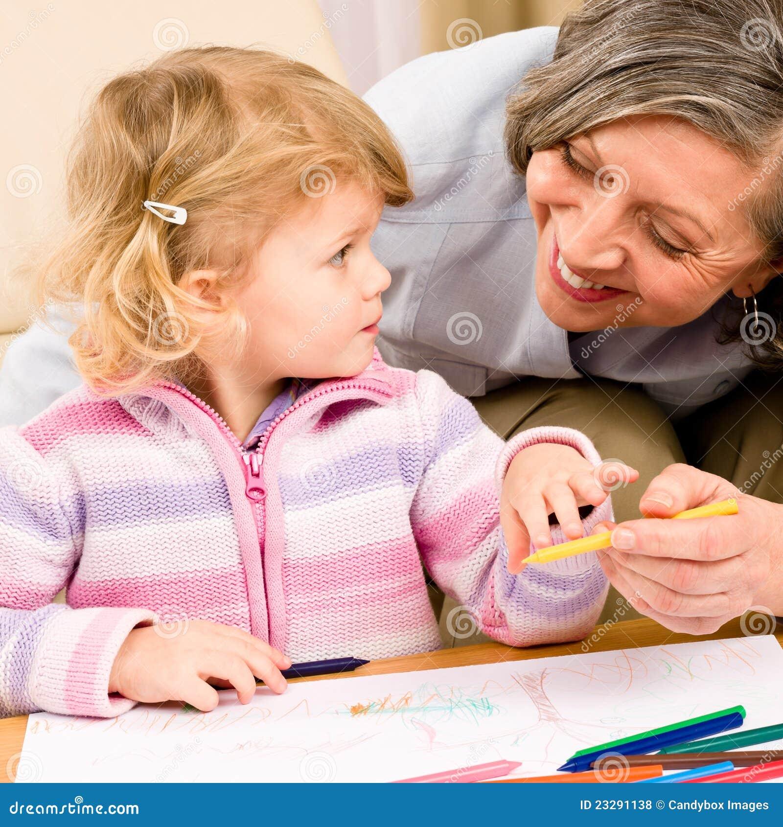 Liten flicka med farmodern som tillsammans tecknar