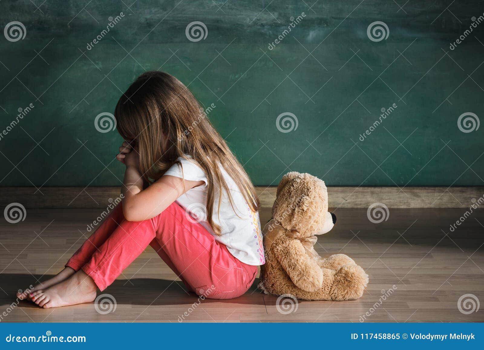 Liten flicka med nallebjörnen som sitter på golv i tomt rum Autismbegrepp
