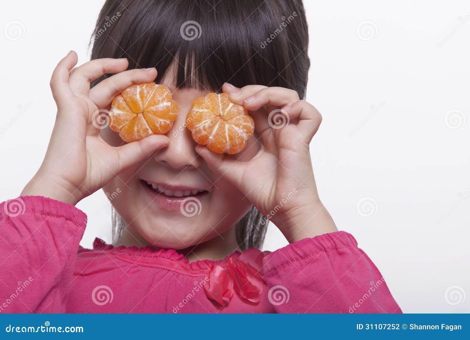 Liten flicka med smällar som rymmer mandariner främsta av hennes head och skuldrastudioskott för ögon,