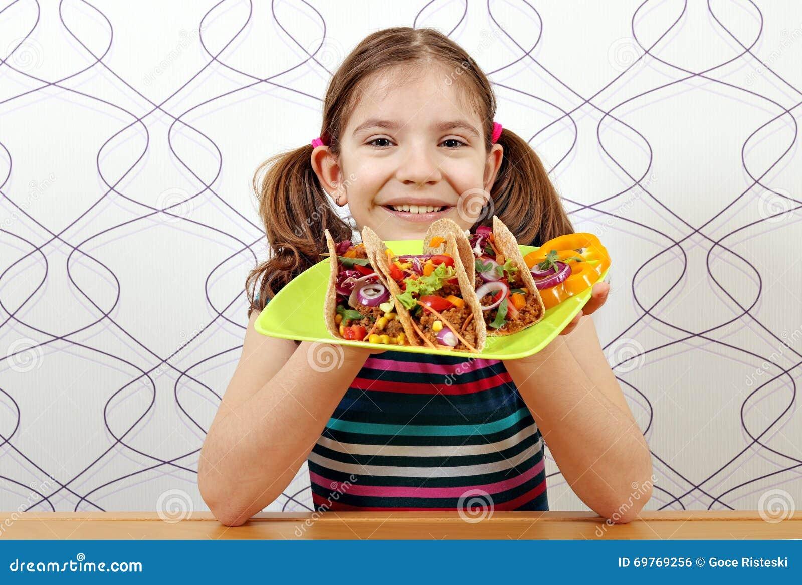 Liten flicka med taco för lunch