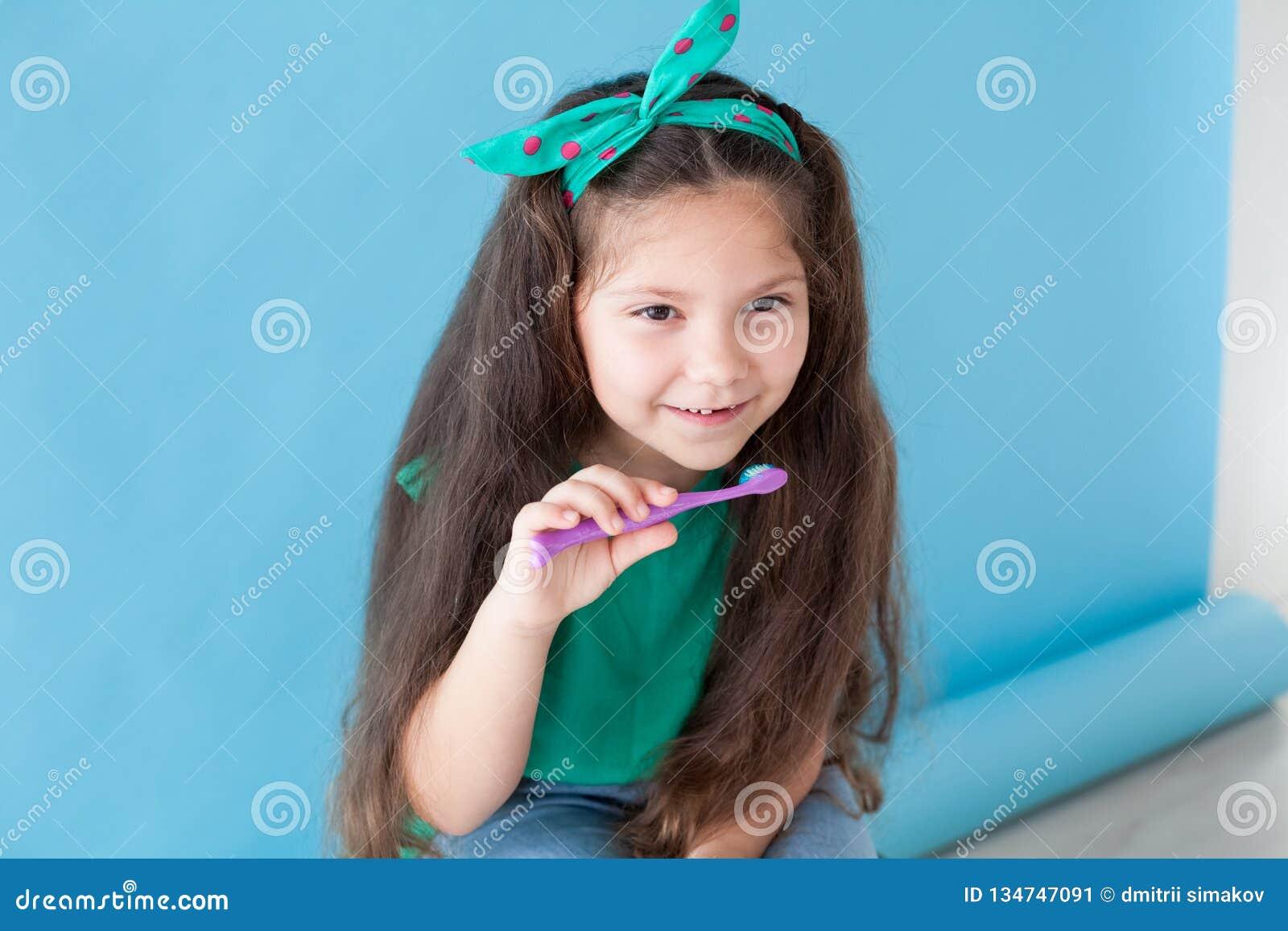 Liten flicka med ut en tand med en tandborstebuckla