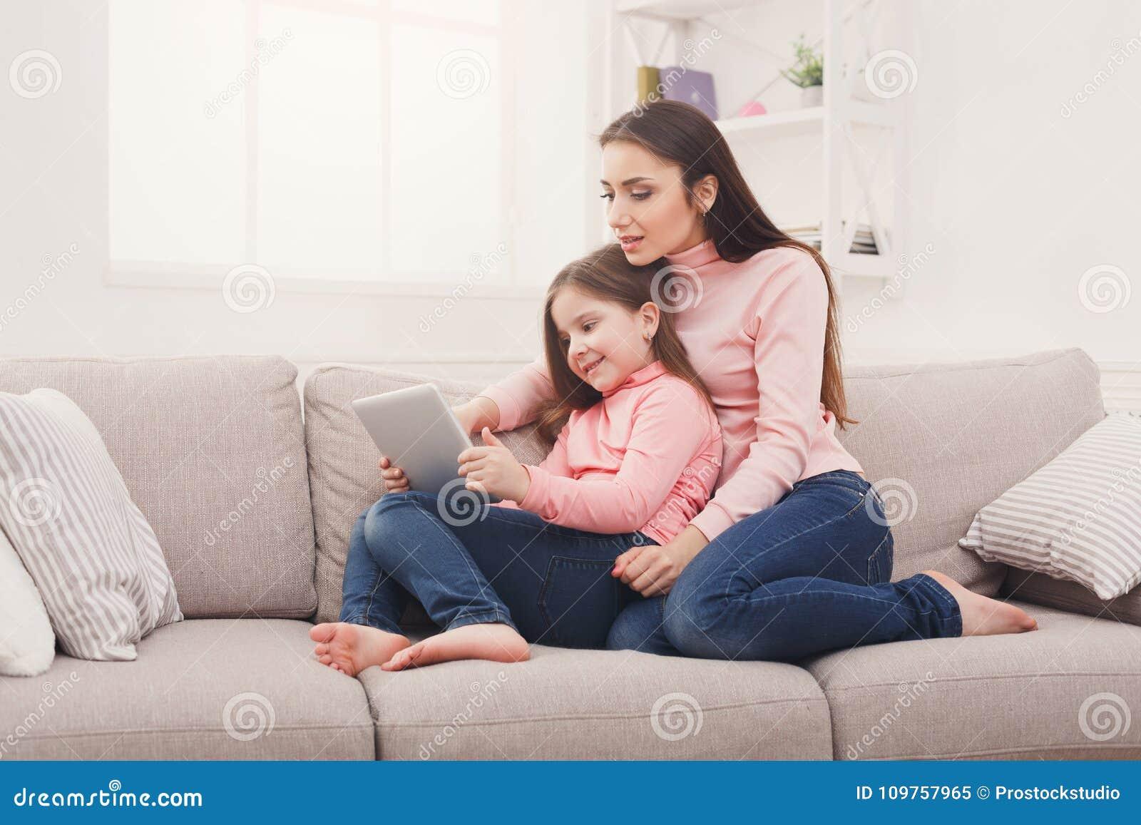 Liten flicka och hennes mamma som hemma använder en minnestavla