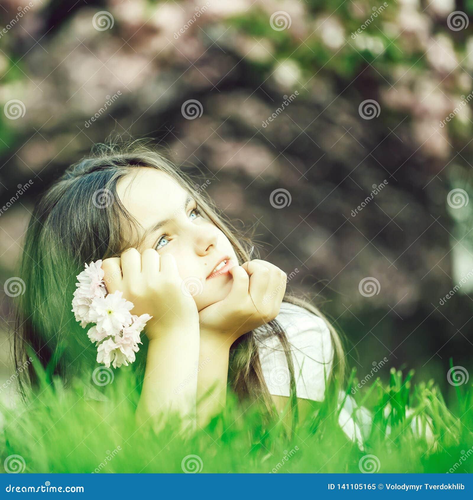 Liten flicka på gräs i blom