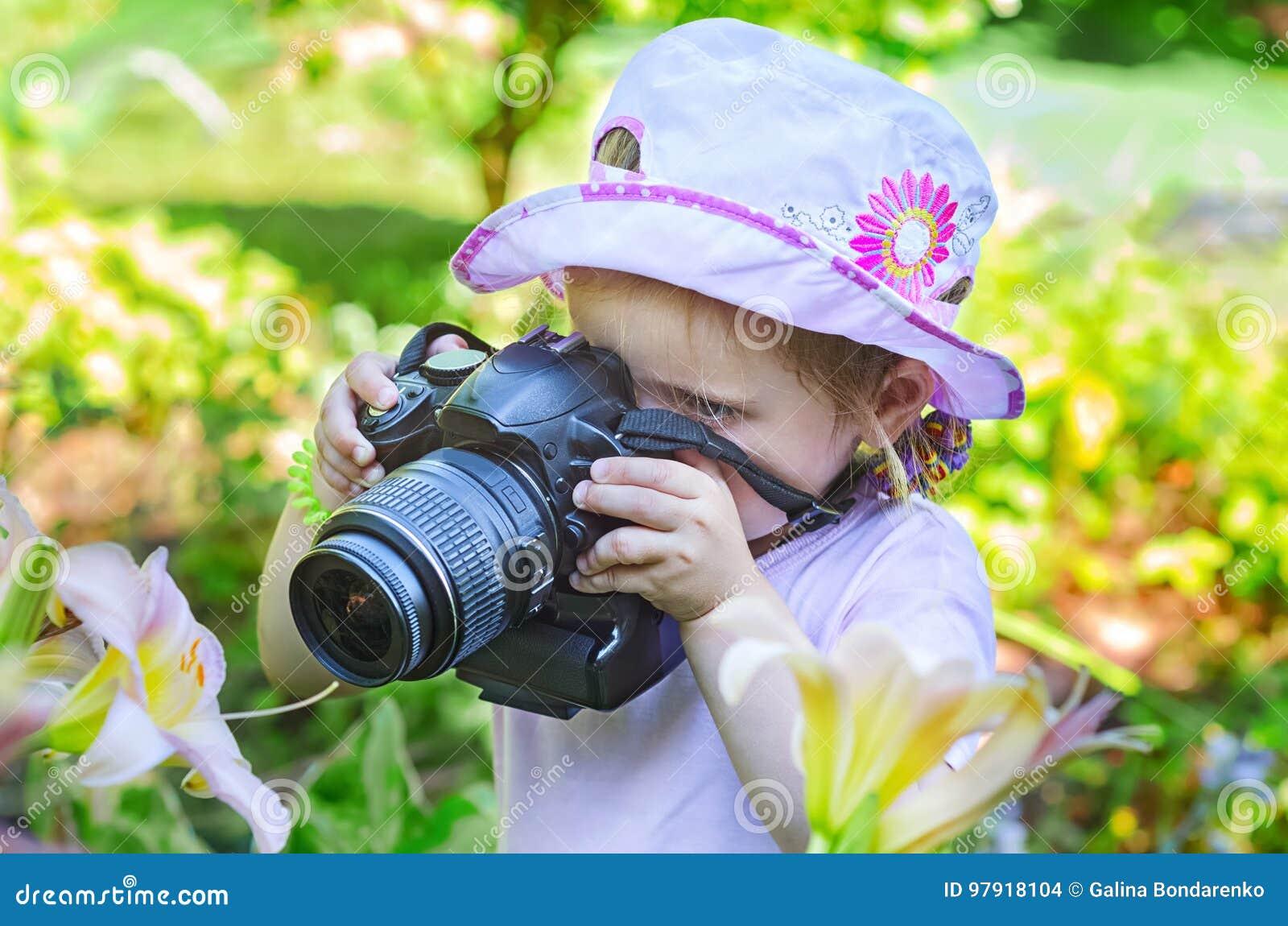 Liten flicka som fotograferar blommor