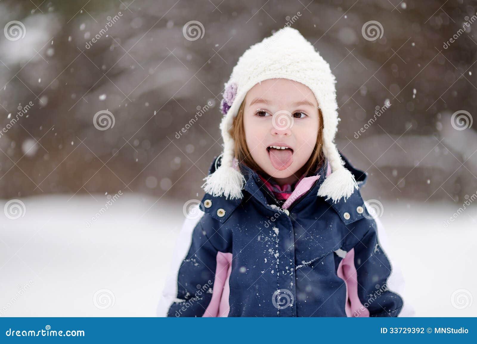 Liten flicka som har gyckel på vinterdag