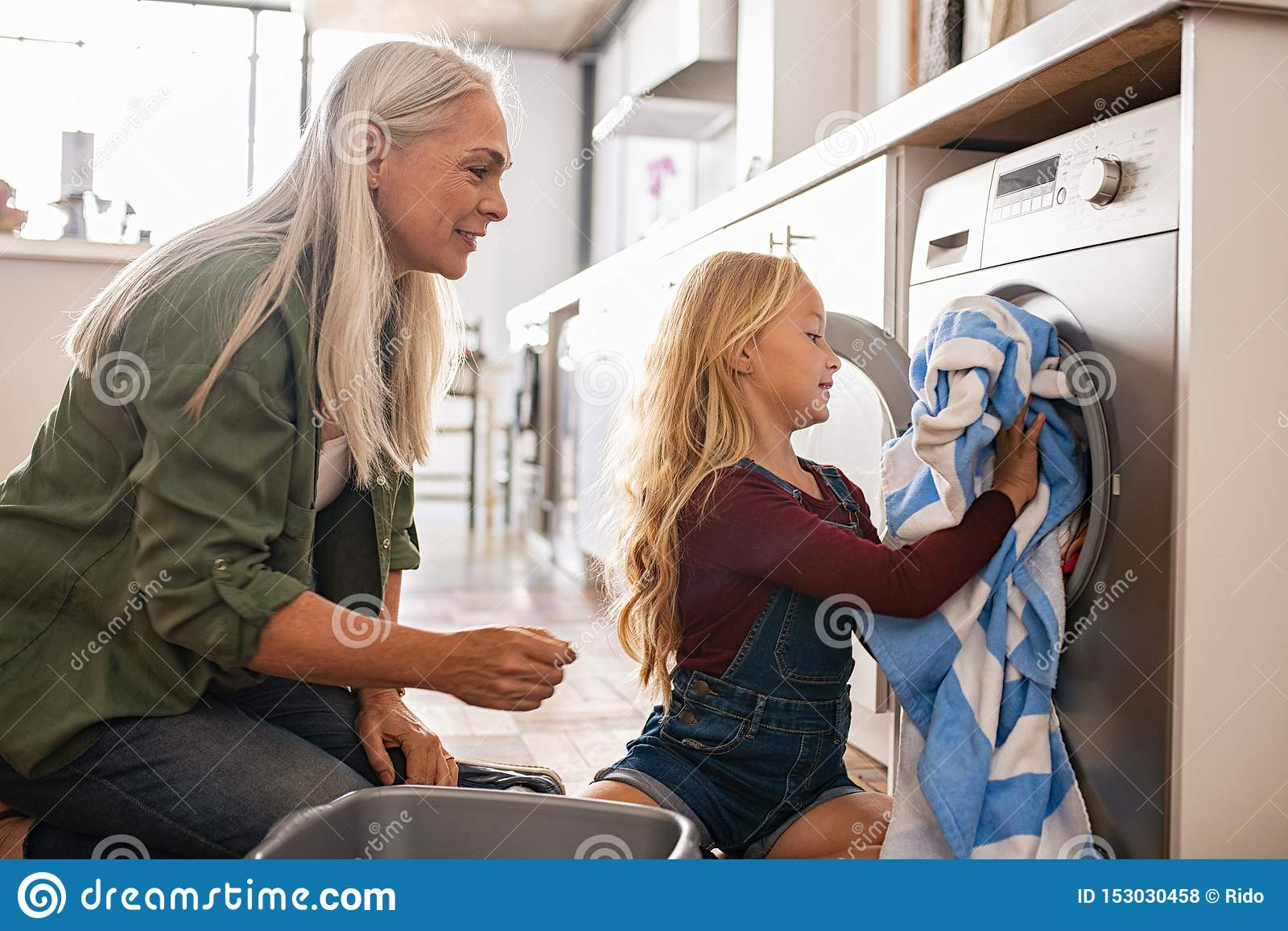Liten flicka som laddar tvagningmaskinen
