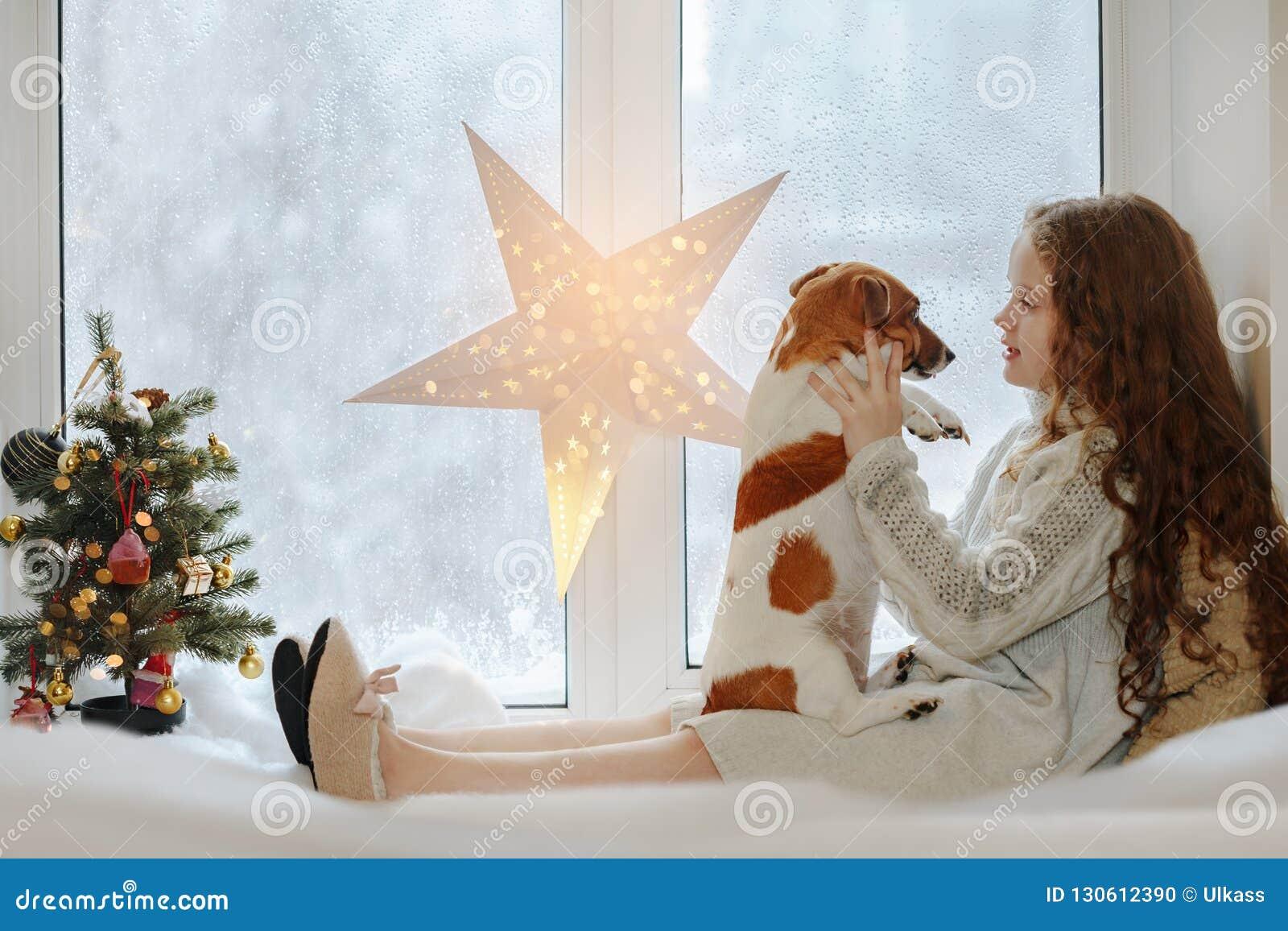 Liten flicka som omfamnar hennes valphund och att sitta på fönster och waiti
