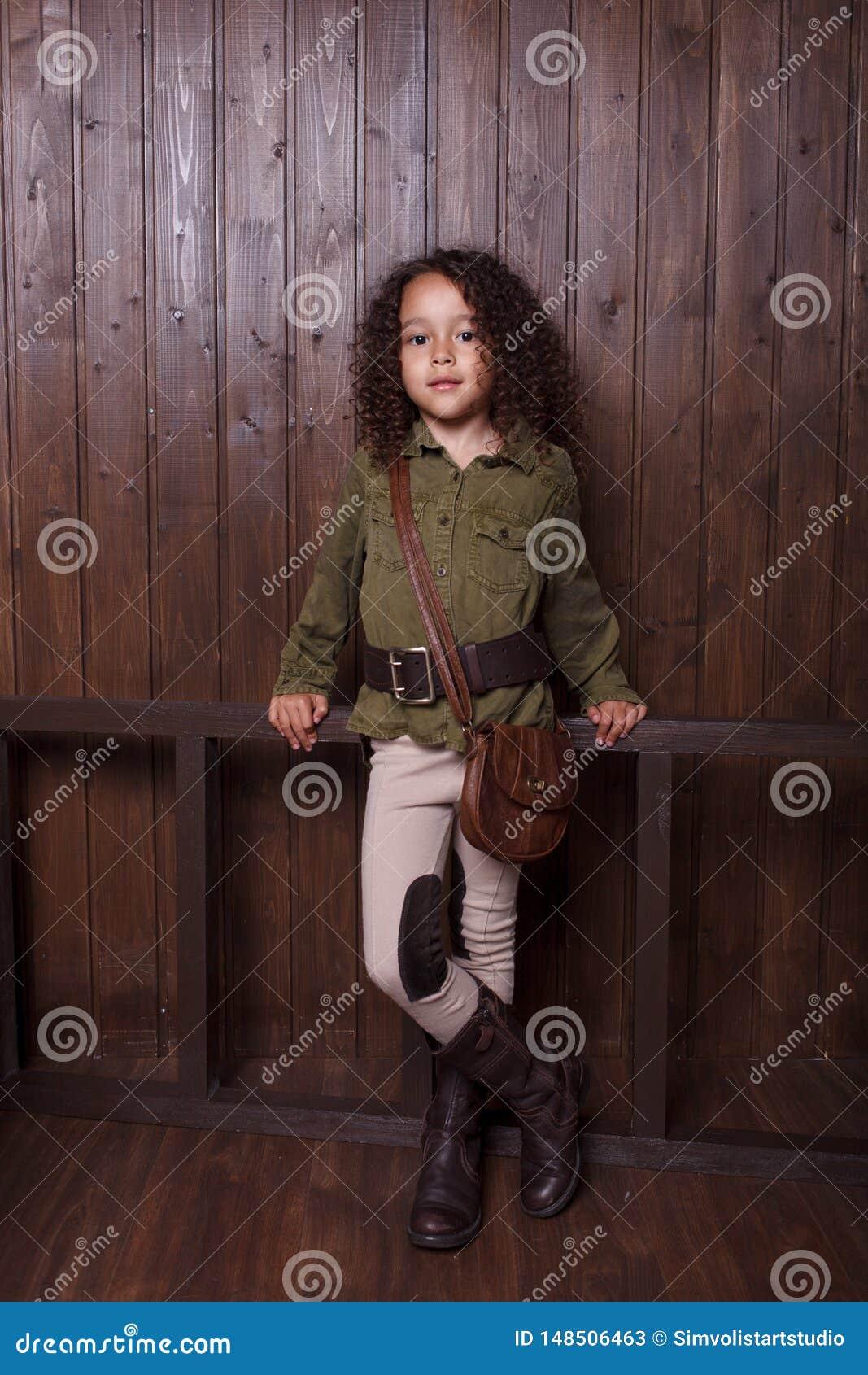 Liten flicka som poserar mot bakgrunden av en trävägg