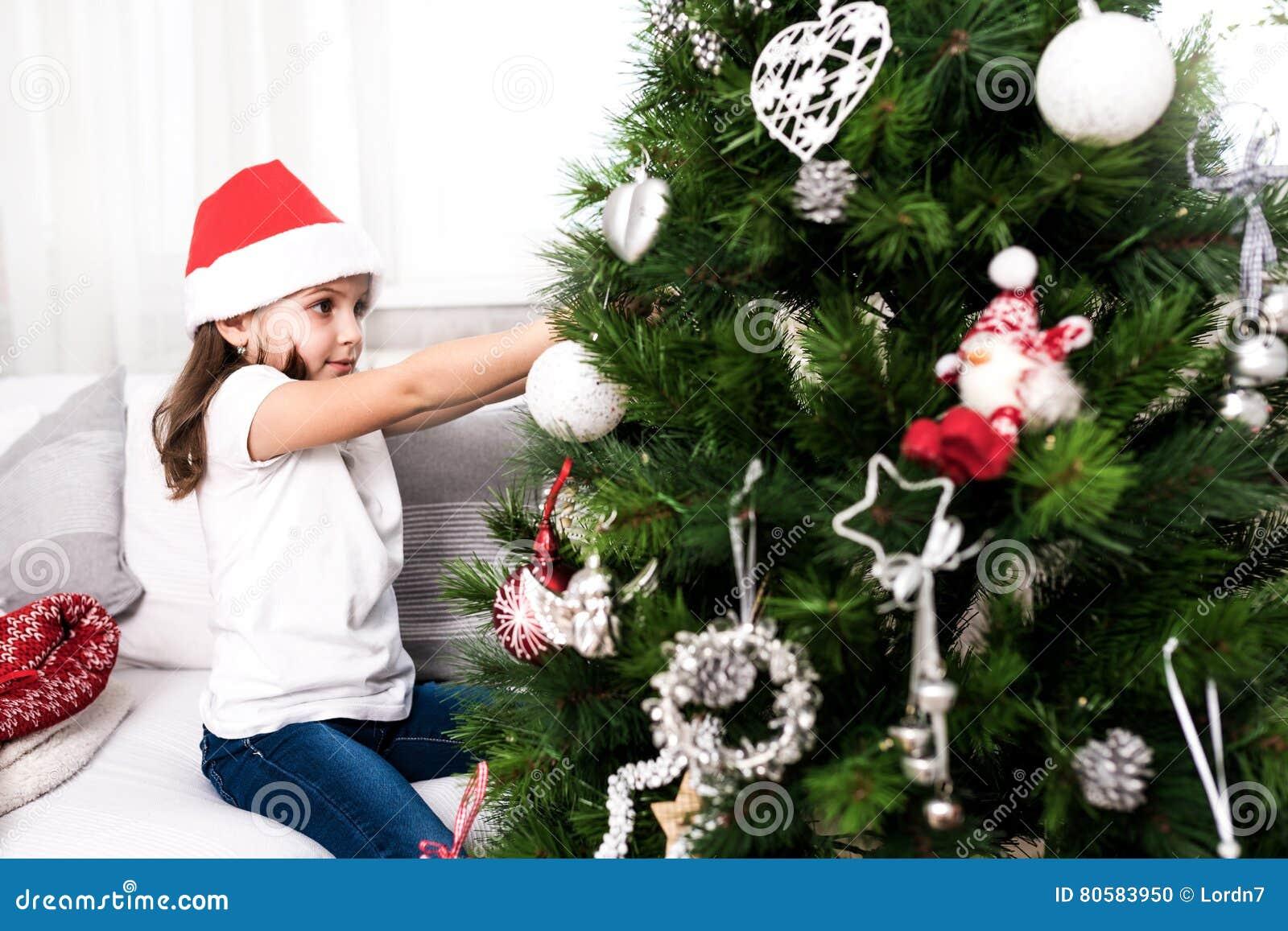 Liten flicka som sätter christmassträdprydnader