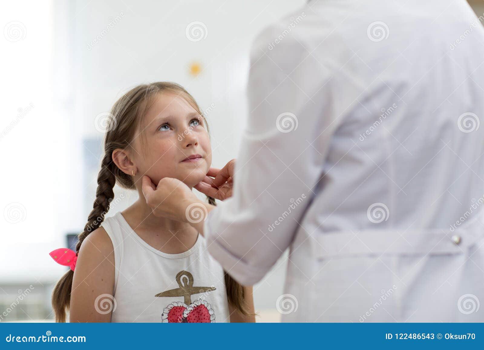 Liten flicka som ser doktorn som som testar hennes tonsillar