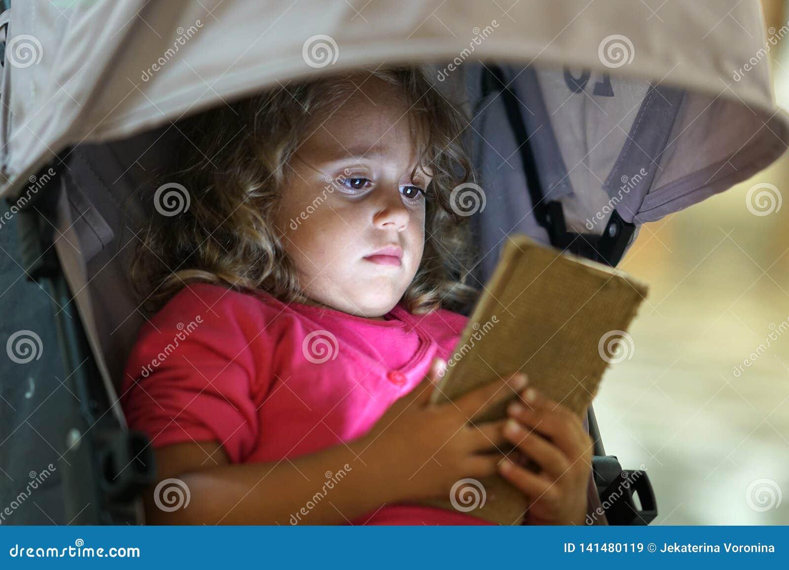 Liten flicka som ser mobiltelefonen även om på semester i Paros