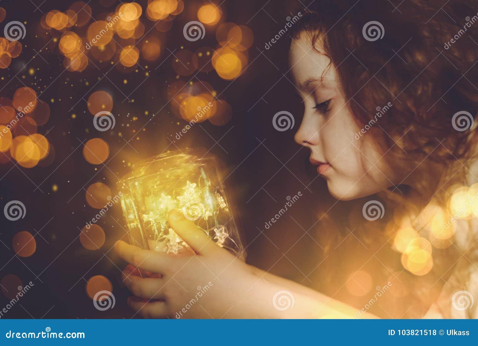 Liten flicka som ser på den magiska jullampan