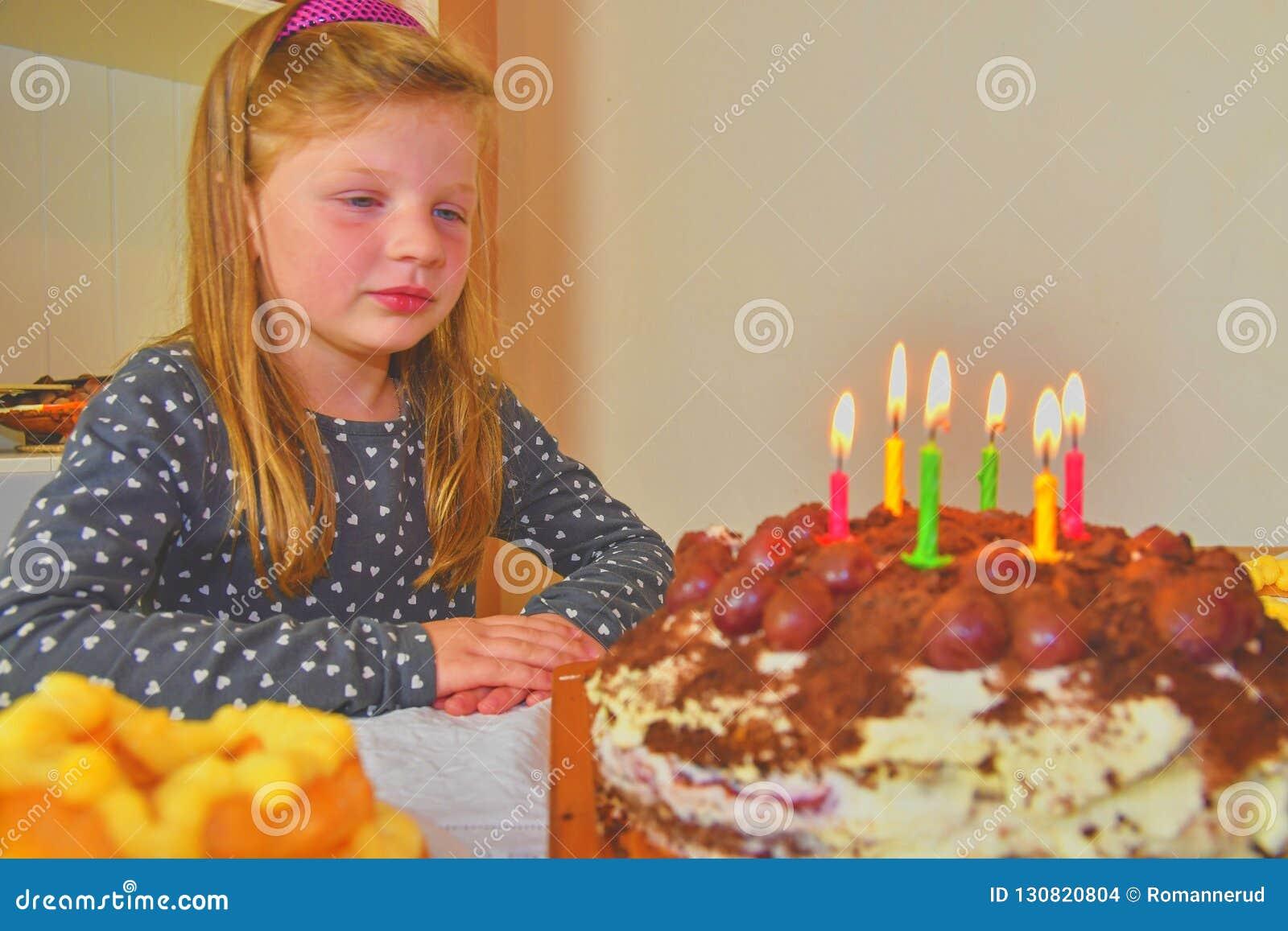 Liten flicka som ser på hennes födelsedagkaka Liten flicka som firar hennes sex födelsedag Födelsedagkaka och liten flicka