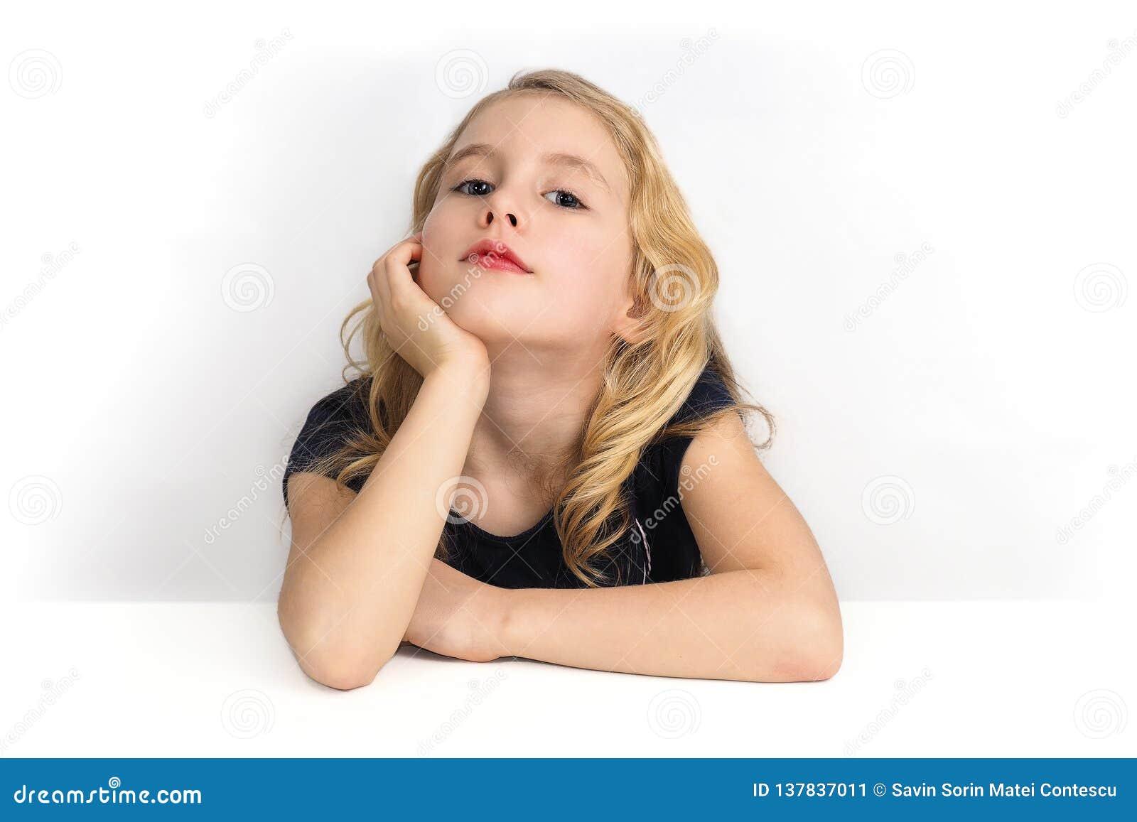 Liten flicka som sitter på en tabell och ser till mig med kuriositet