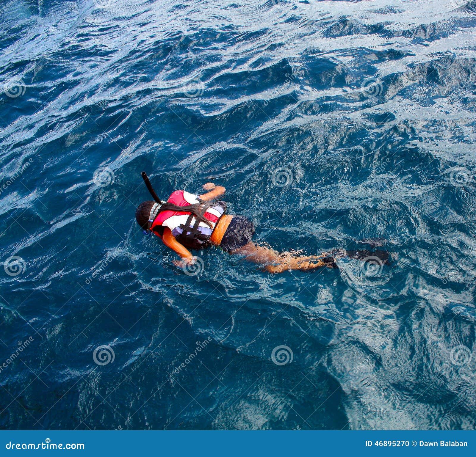 Liten flicka som snorklar i havet