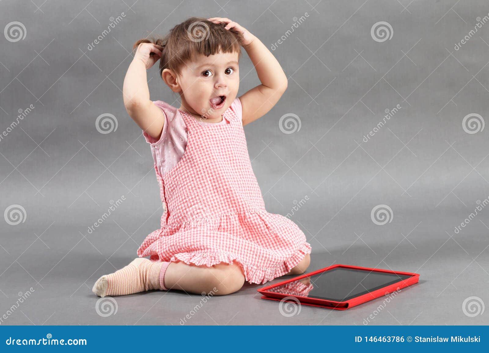 Liten flicka som spelar med minnestavladatoren på golvet