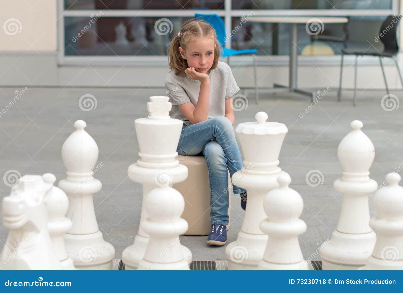 Liten flicka som spelar schackleken