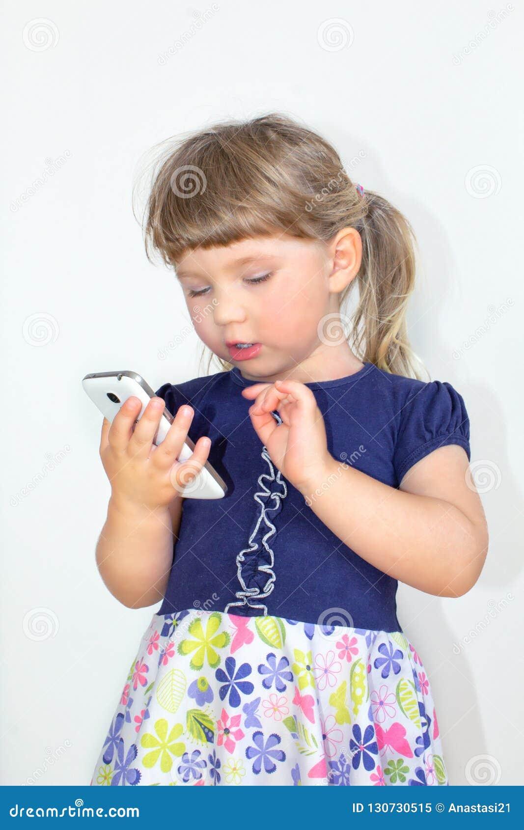 Liten flicka som talar på en mobiltelefon, på en vit bakgrund