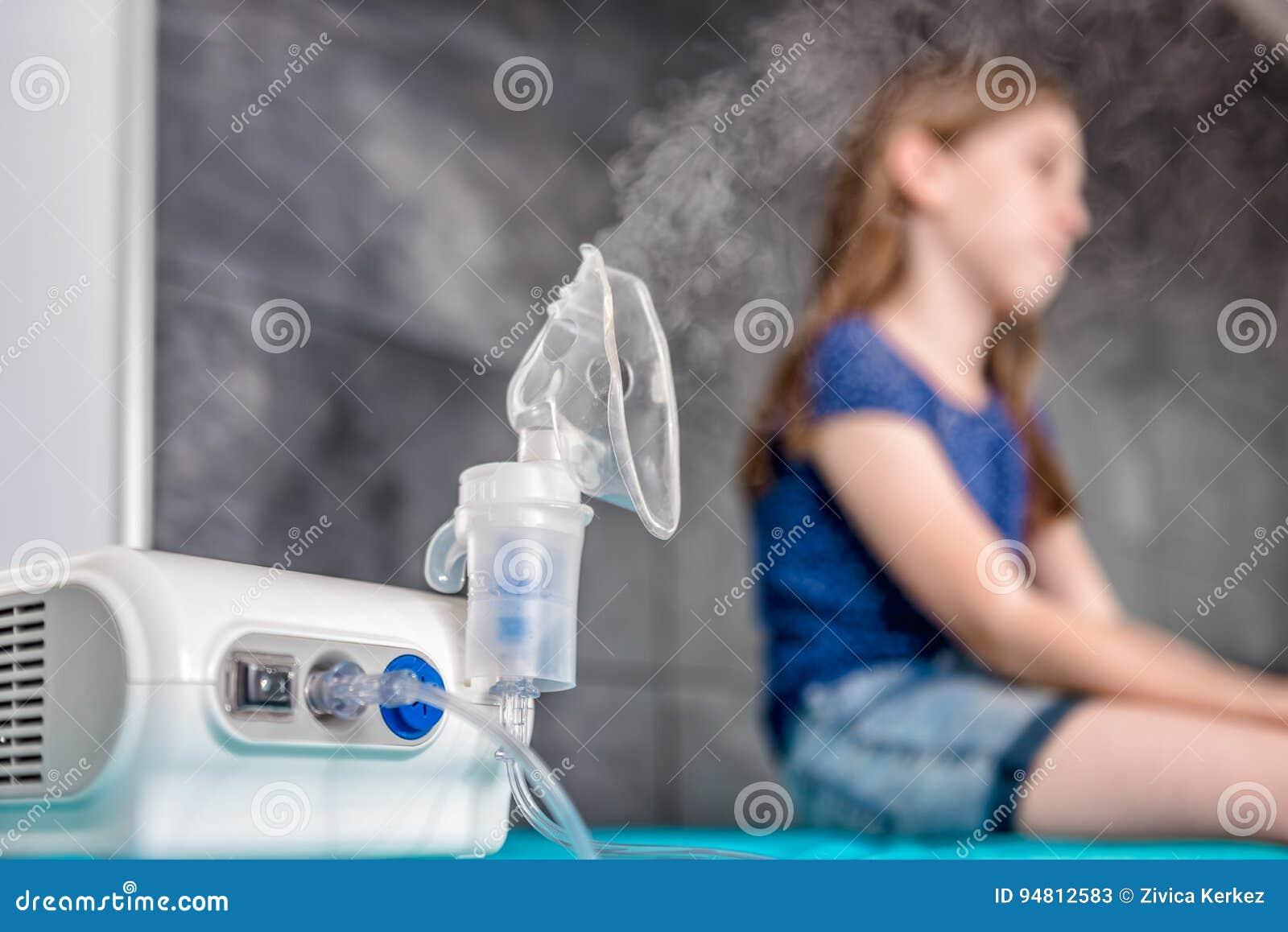 Liten flicka som väntar på medicinsk inandningbehandling med en nebu