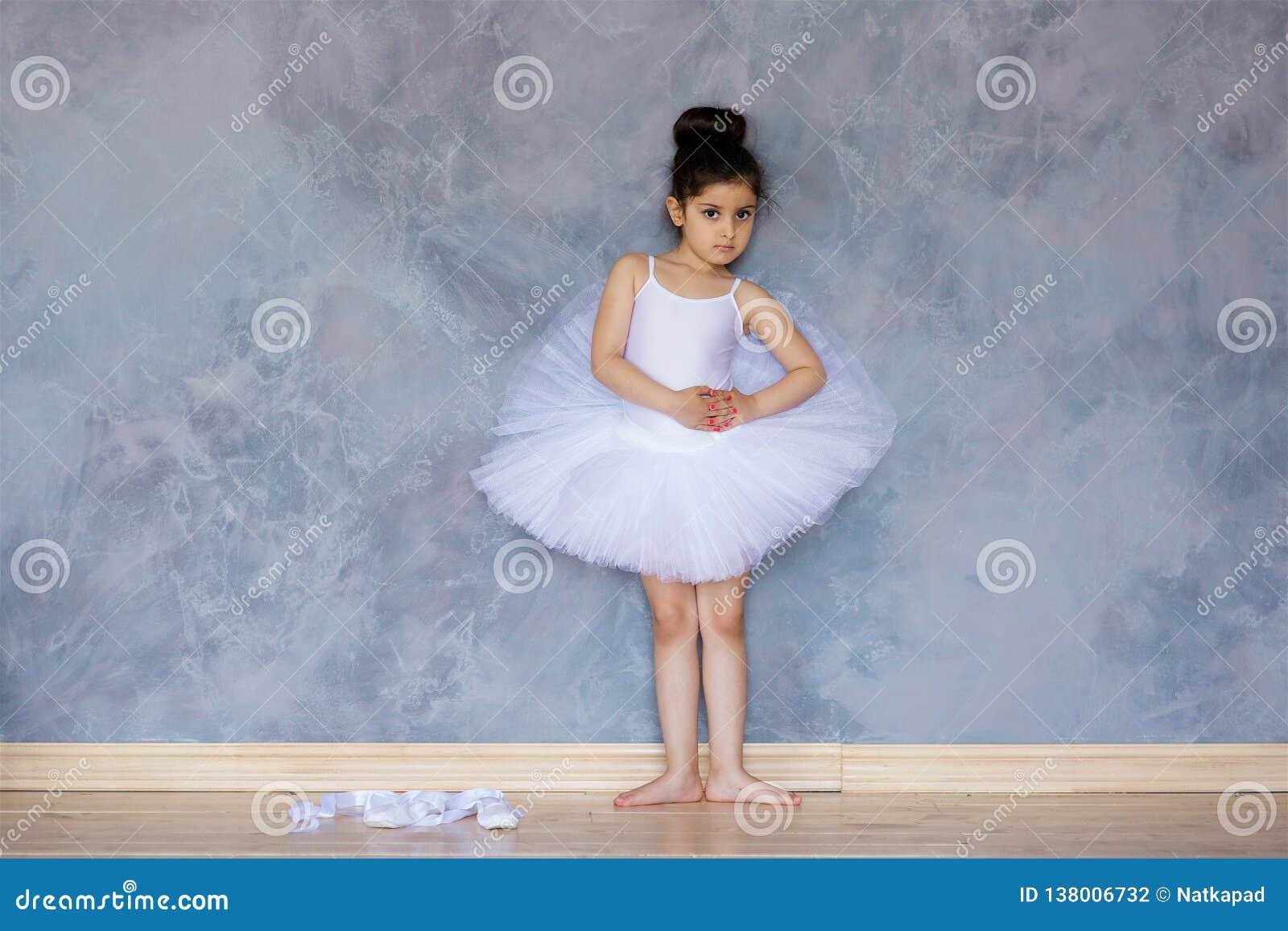 Liten flickaballerina i en vit ballerinakjol