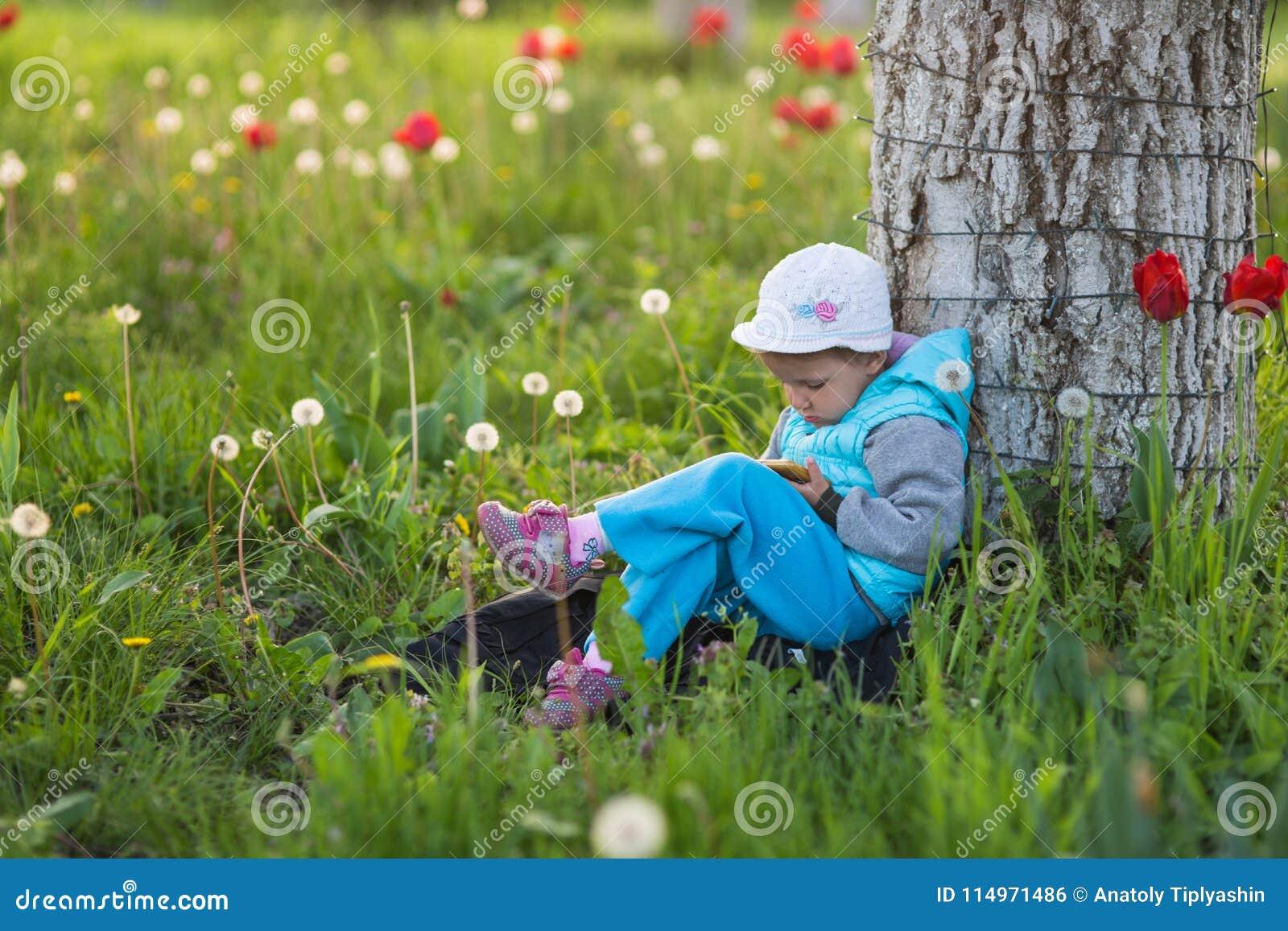 Liten flickabarn i ett fält med grönt gräs och den blommande tulpan