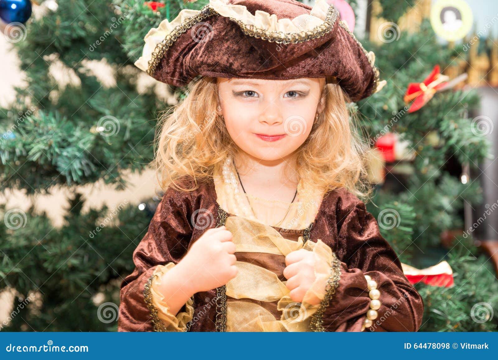 Liten flickabarnet klädde som piratkopierar för allhelgonaafton på bakgrund av julgranen