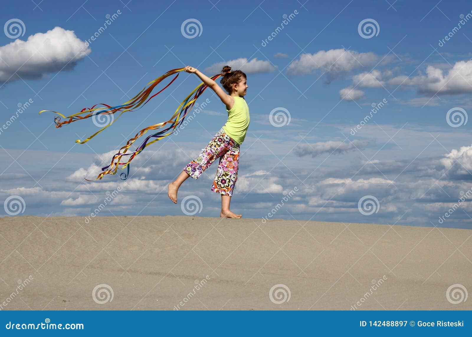 Liten flickalek och vinka med färgrika band