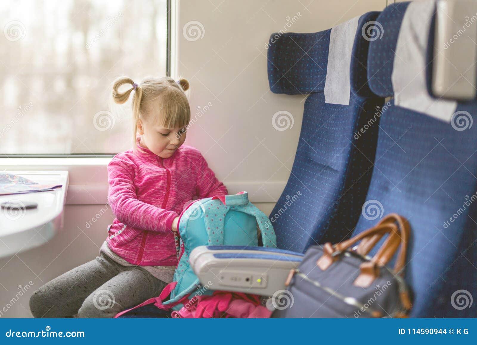 Liten flickalopp med drevet Lura sammanträde i bekväm stol och att se i ryggsäck Saker som ska tas med på järnvägtur med
