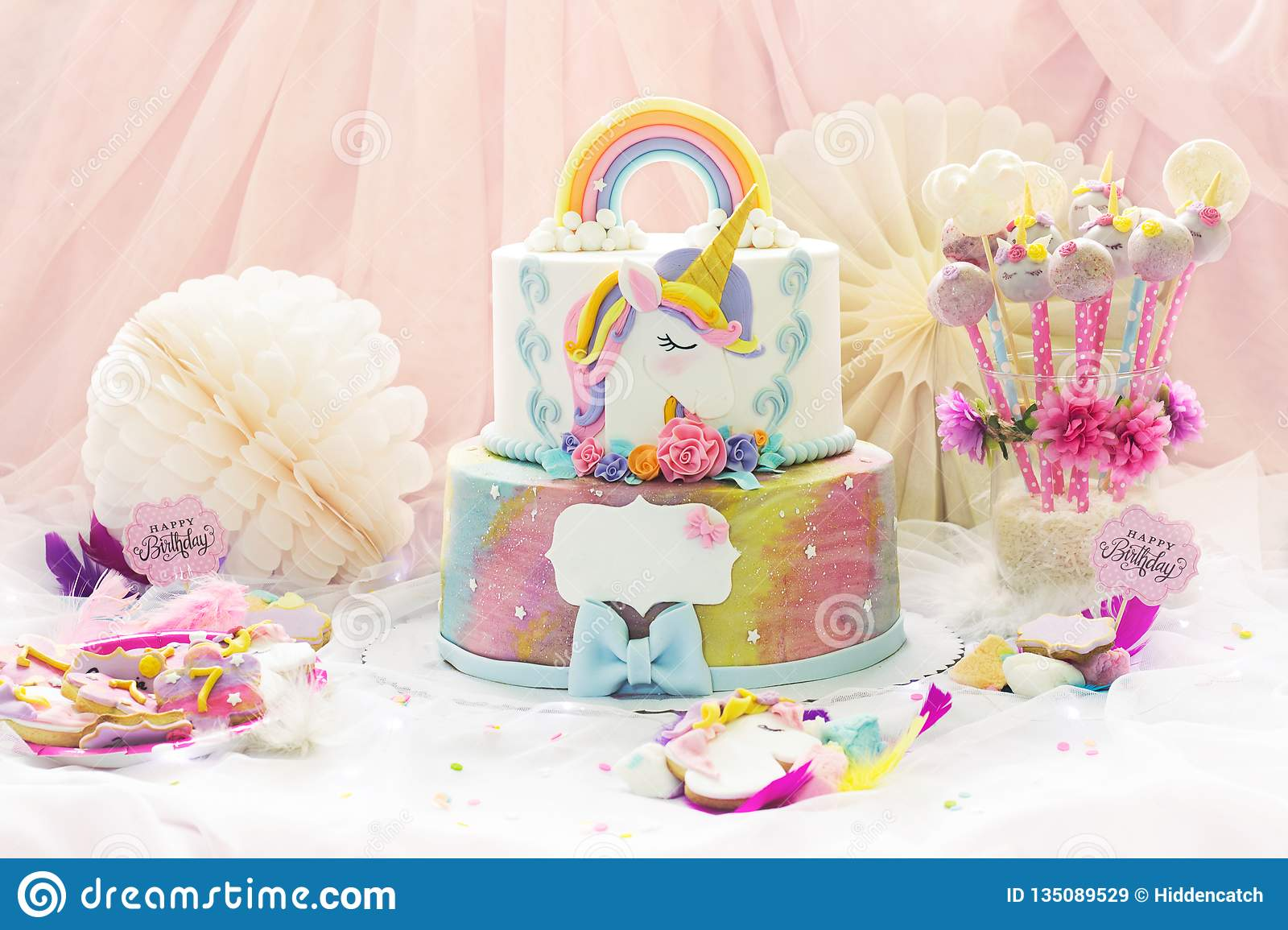 Liten flickas födelsedagparti; efterrätttabell med enhörningkakan, kaka-pop, sockerkakor och födelsedaggarnering