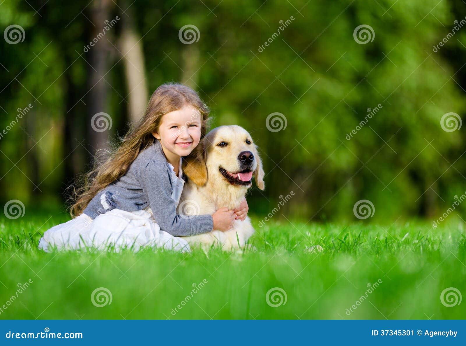 Liten flickasammanträde på gräset med golden retriever