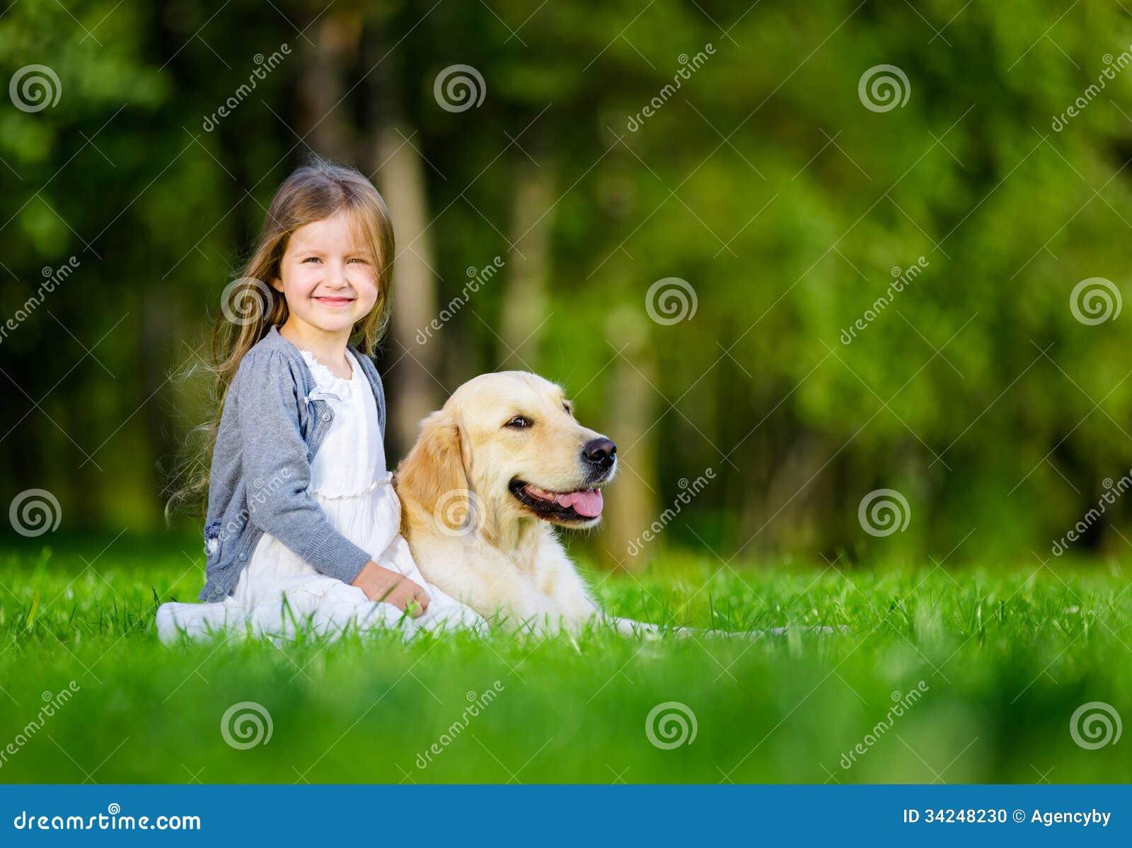 Liten flickasammanträde på gräset med labrador retriever