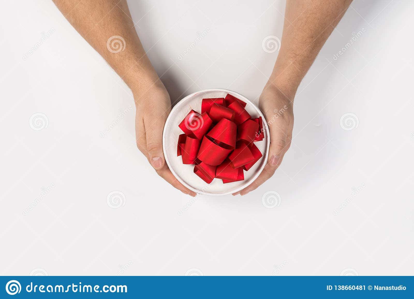 Liten gåva med den röda bandpilbågen i manhänder på vit bakgrund