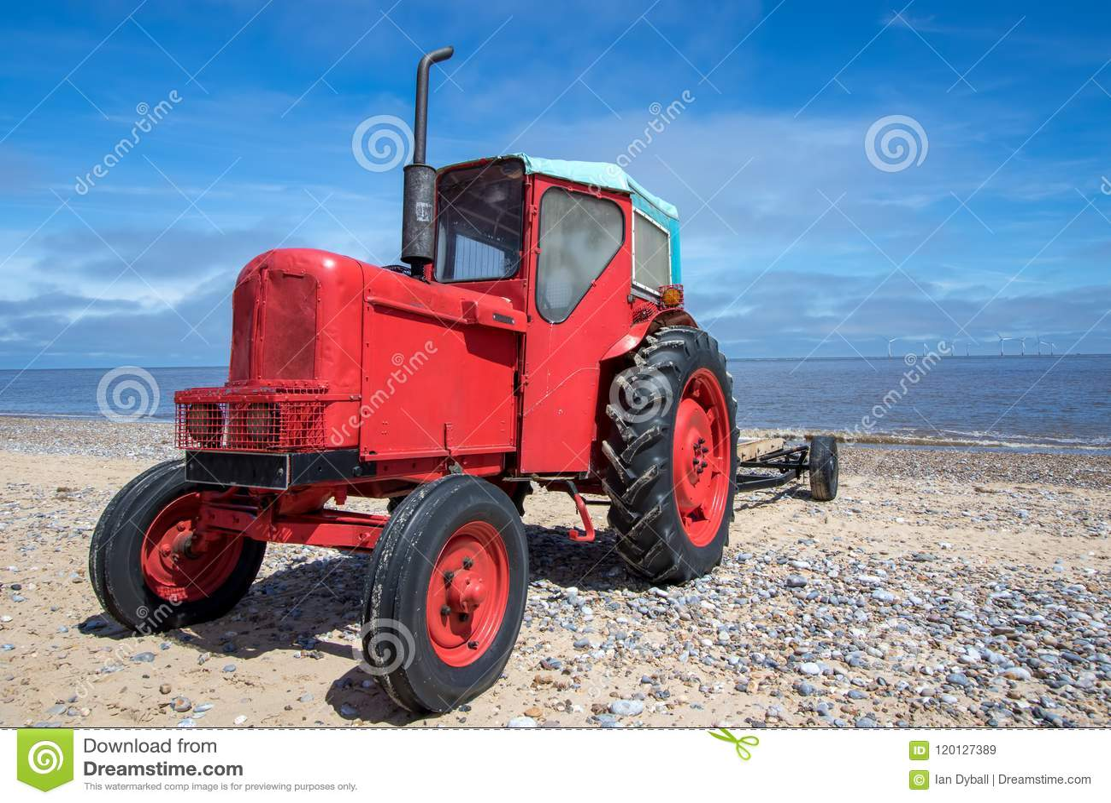 Liten gammal röd diesel- traktor på stranden