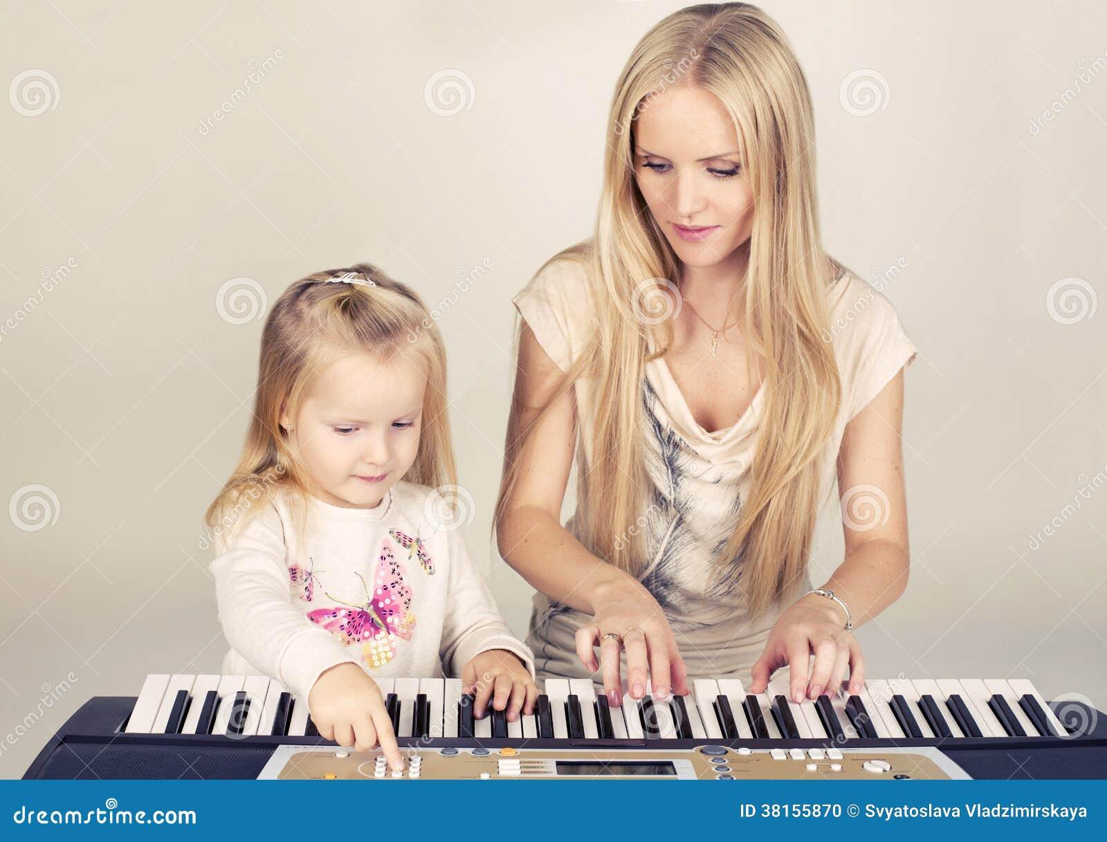 Liten gullig flicka med hennes mamma som spelar på syntet