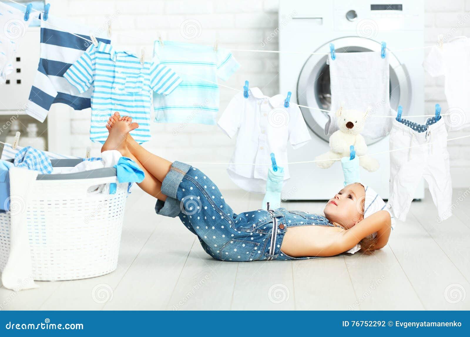 Liten hjälpreda tröttad barnflicka som tvättar kläder och som vilar i laund