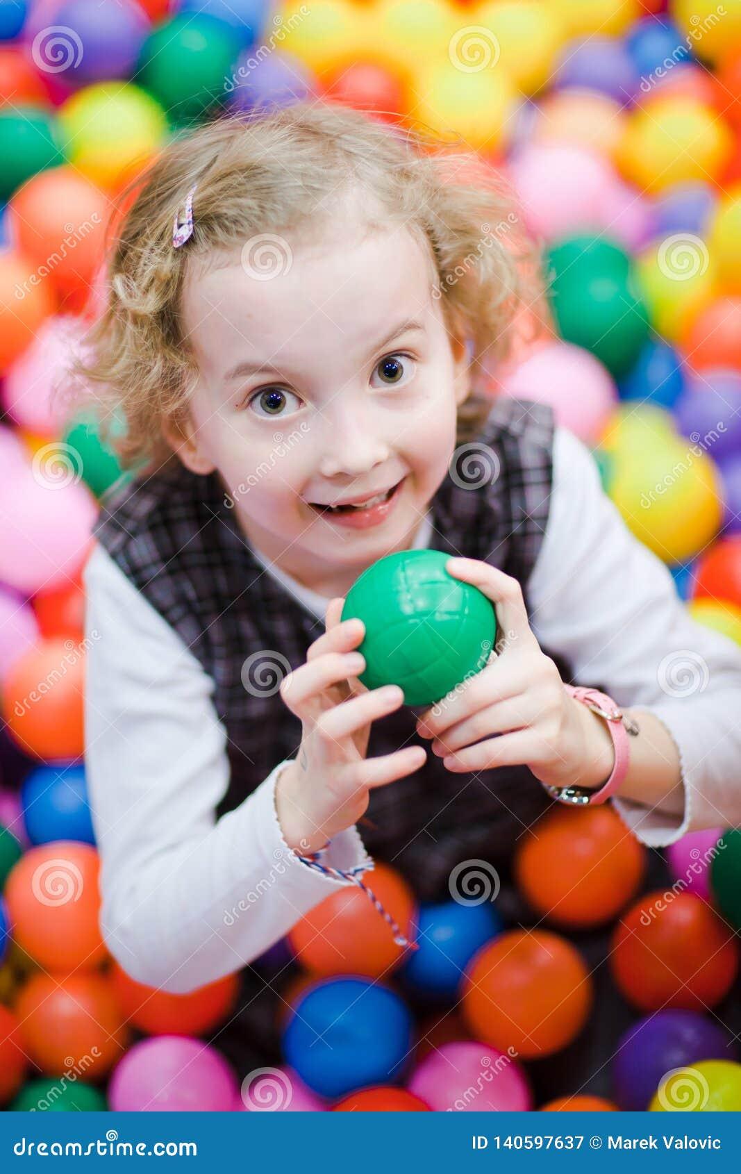 Liten le flicka som sitter bland mycket färgrika bollar - grund fokus på ögon