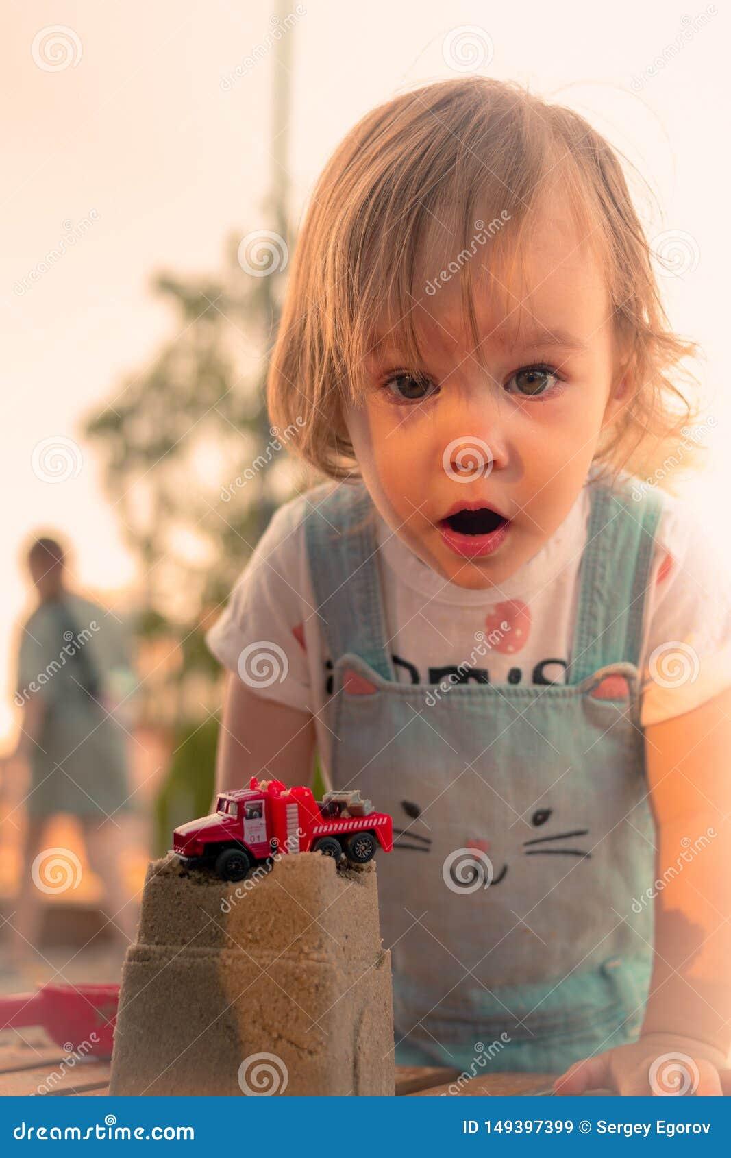 Liten le flicka som spelar med sandslotten och den röda billeksaken i sandlåda