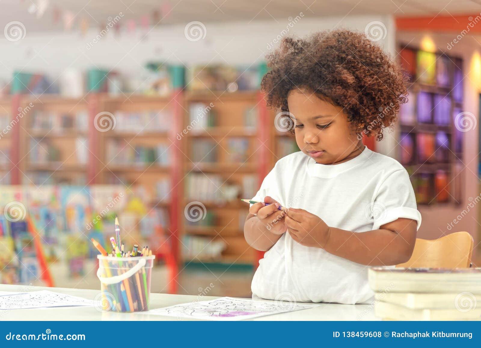 Liten litet barnflickakoncentrat på teckning Afrikansk flicka för blandning att lära och spela i förträningsgruppen Barn tycker o
