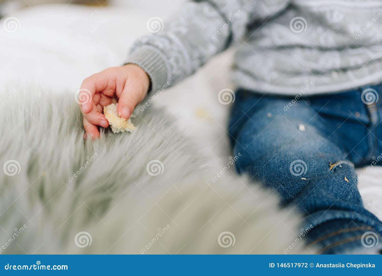 Liten litet barnpojkes hand med ett mellanmål