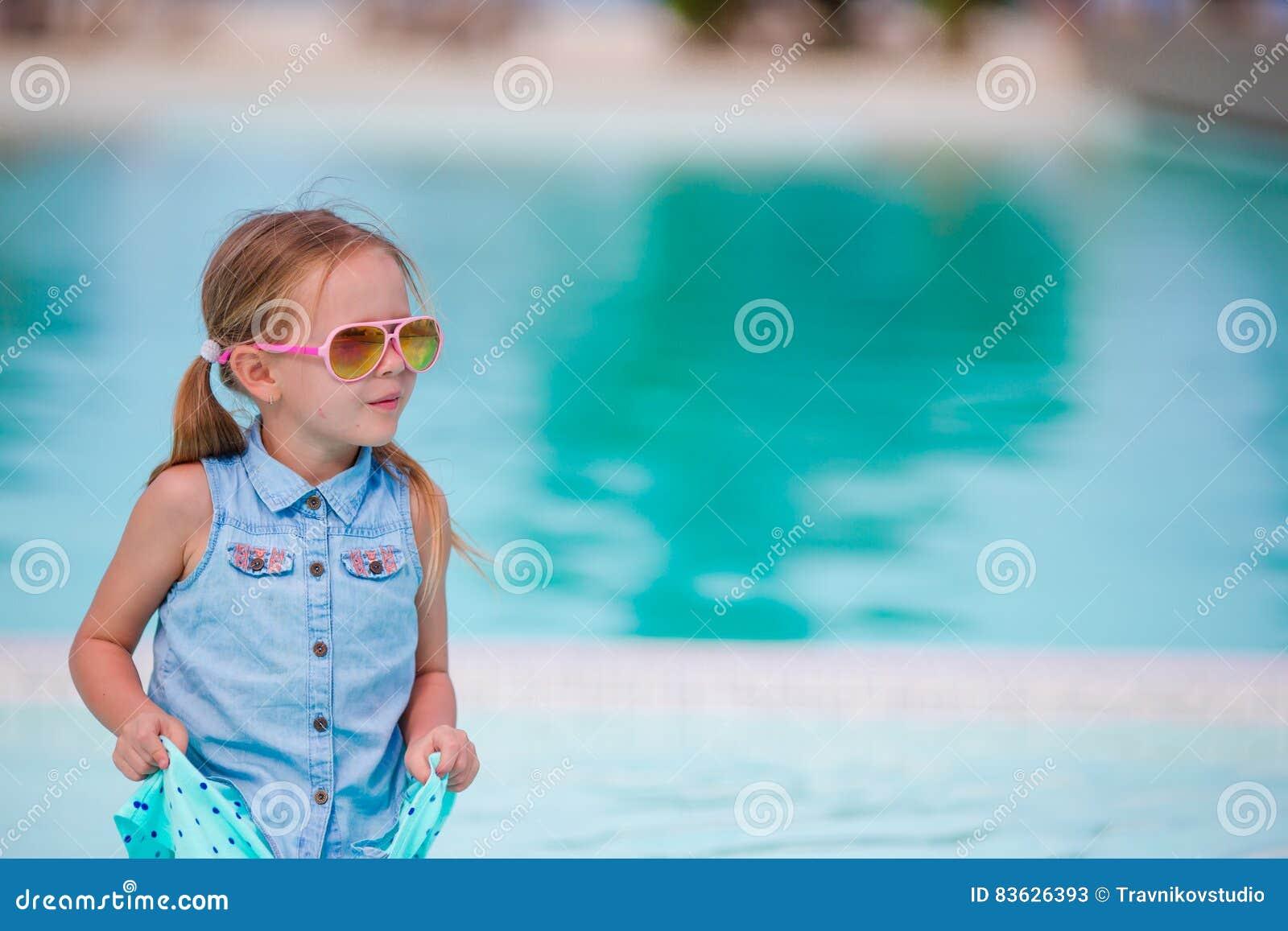 Liten lycklig förtjusande flicka på kanten av den utomhus- pölen