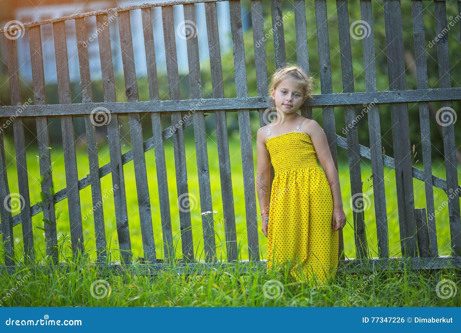 Liten lycklig flicka i gul klänning nära trästaketet i byn