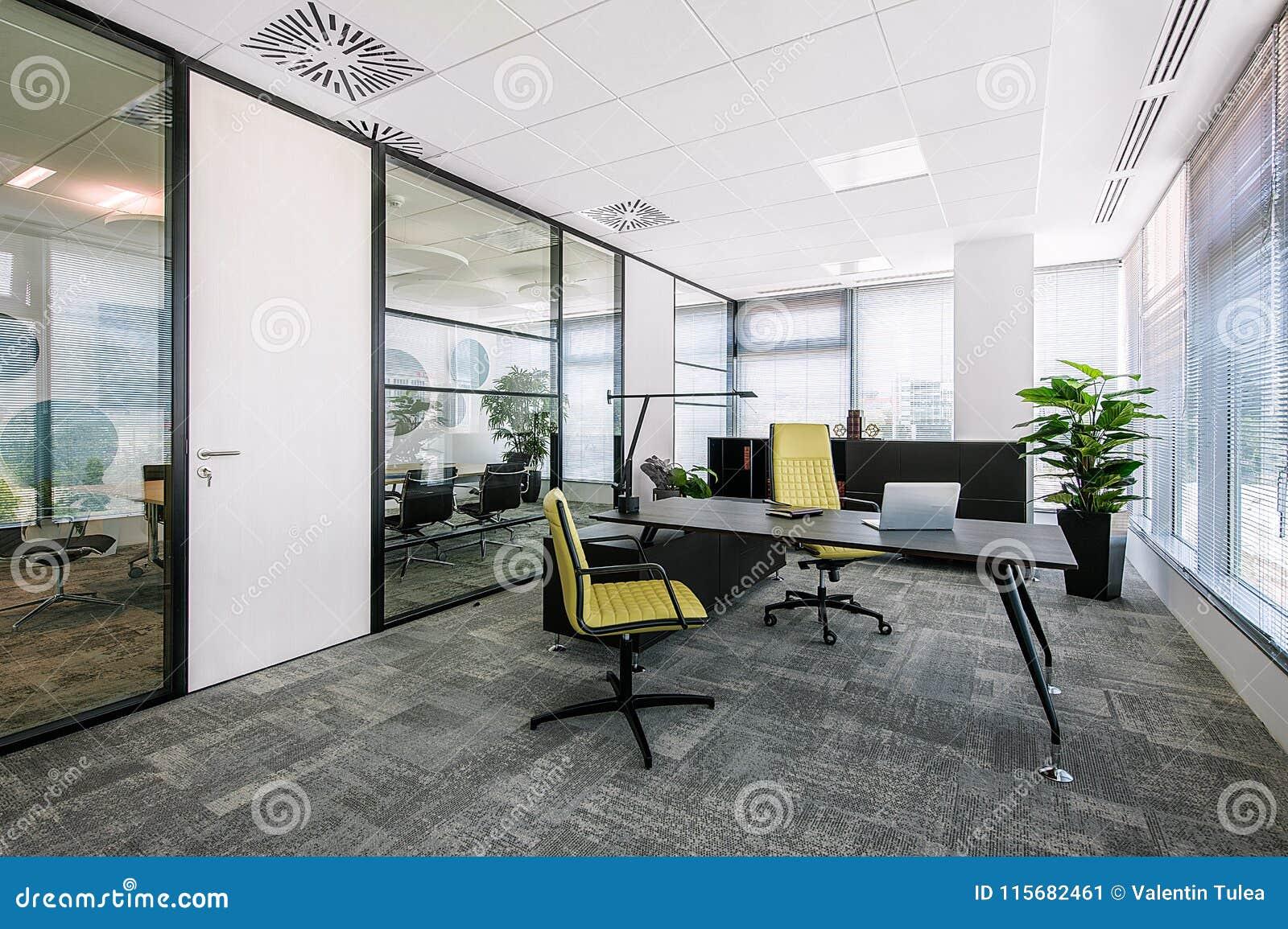 Liten modern kontorsstyrelse- och mötesruminre med skrivbord, stolar