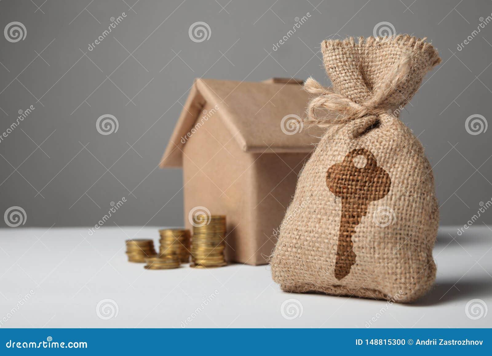 Liten påse med det nyckel- tecknet och guld- mynt på bakgrunden av hantverkdiagramet av huset Det uthyrnings- priset, köper godsf