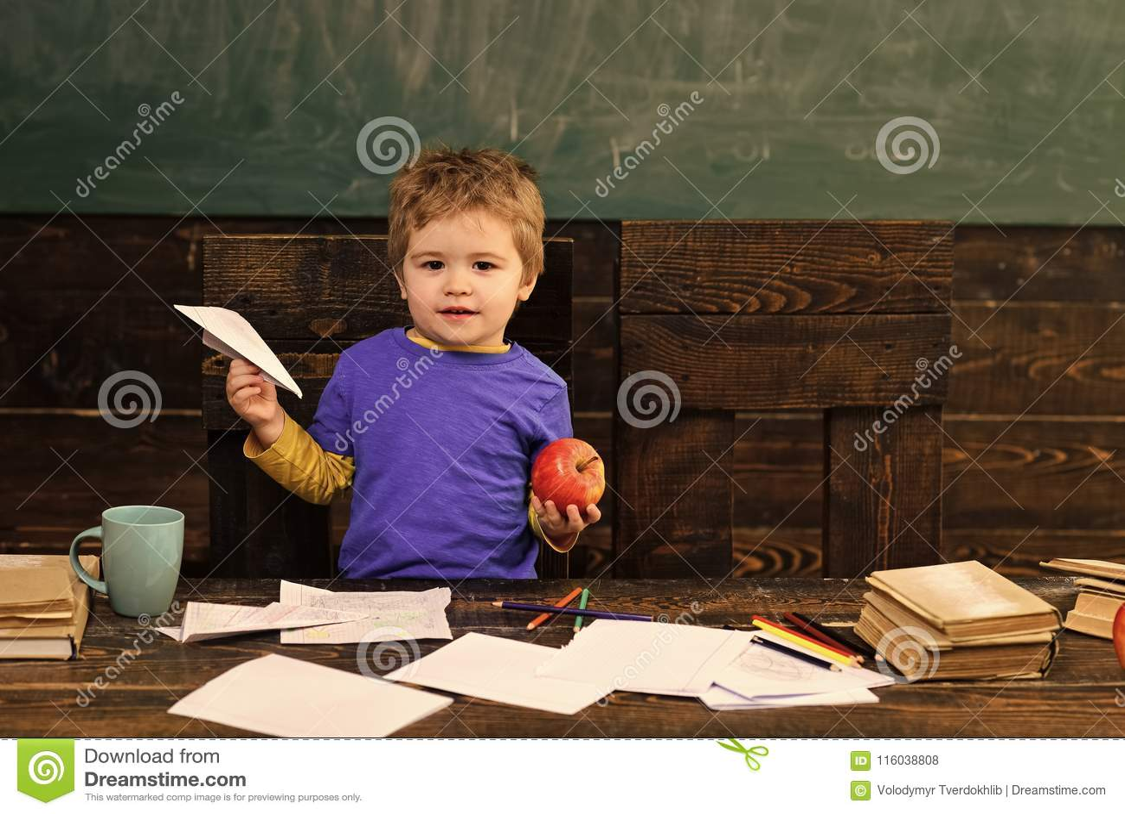 Liten pojke med det pappersnivån och äpplet i klassrum Unge på grundskolan Gulligt barn bak tabellen med förskriftsböcker