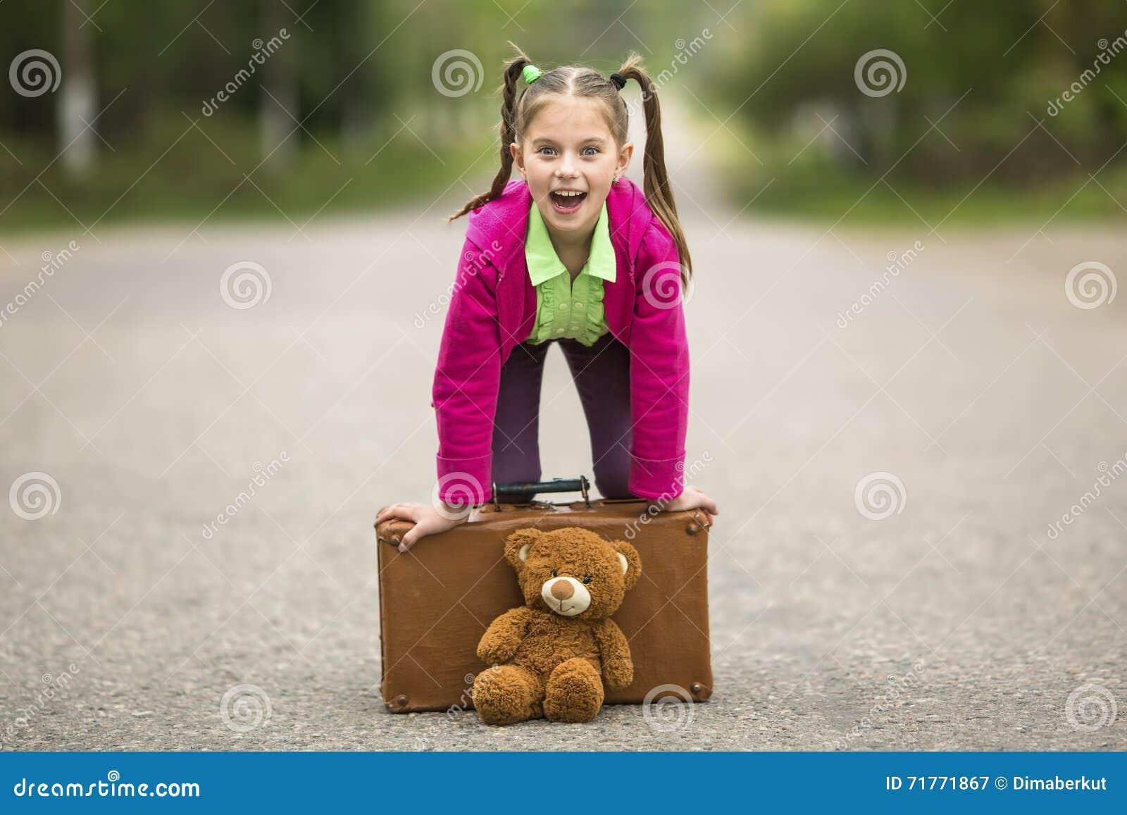 Liten rolig flicka på vägen med en resväska och en nallebjörn Lyckligt