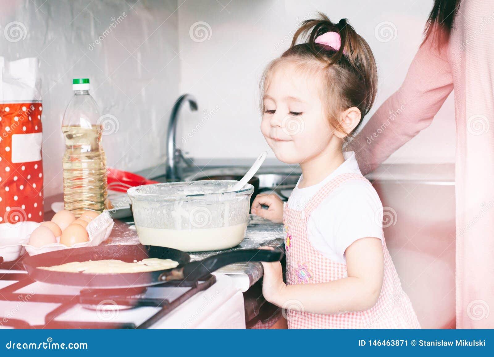 Liten s?t flicka och hennes modersm?fiskpannkakor p? den traditionella ryska feriekarnevalet Maslenitsa Shrovetide