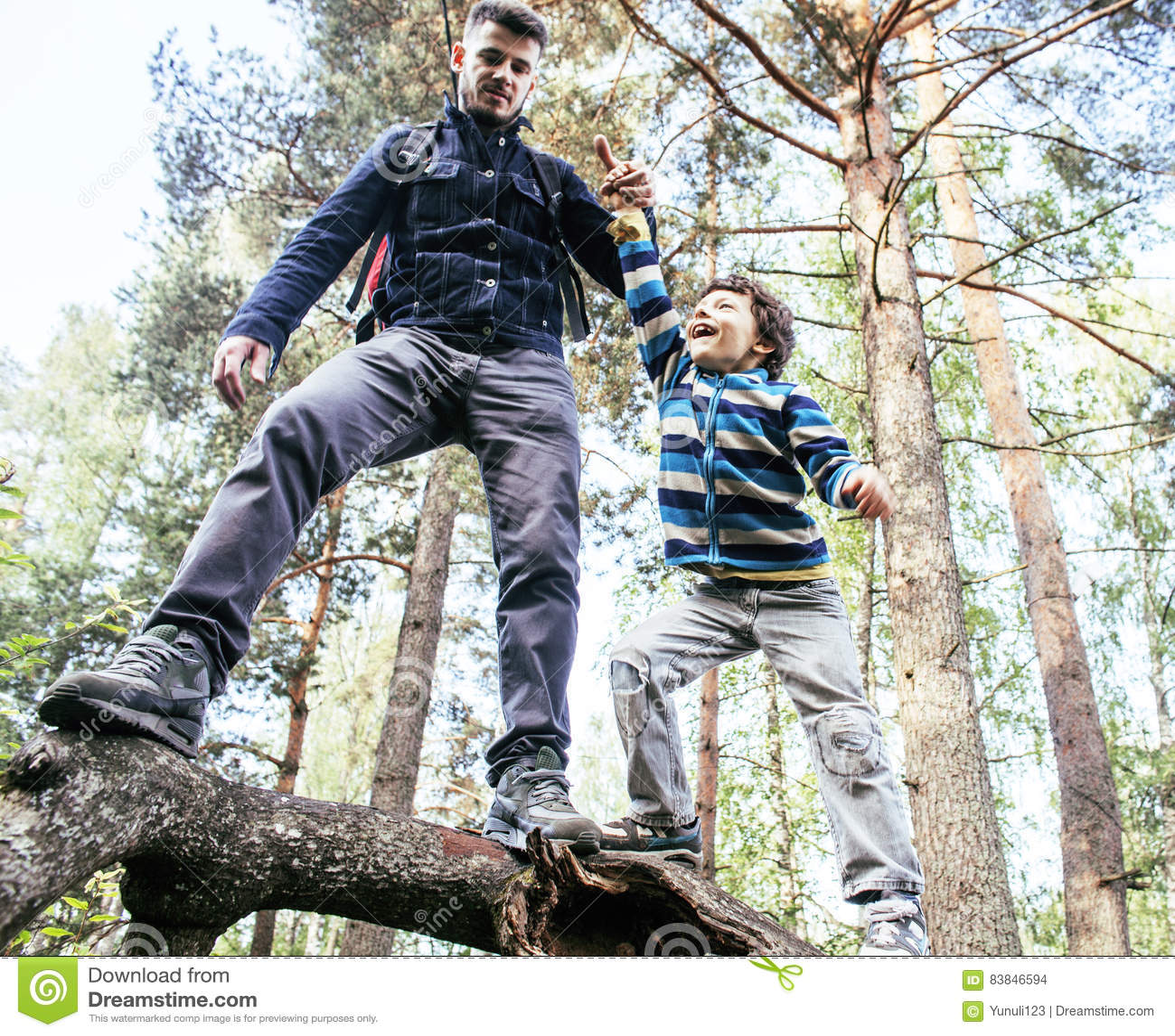 Liten son med faderklättring på träd tillsammans i skogen, livsstilfolkbegrepp, lycklig le familj på sommar